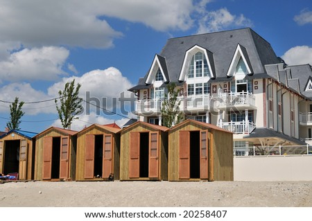 row of beach huts in front of a big villa