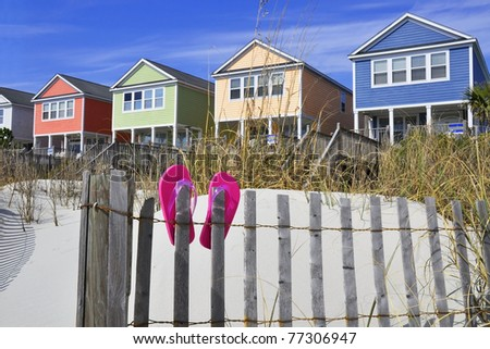 Row of beach rentals on a summer day, pink flip flops on beach fence - stock photo