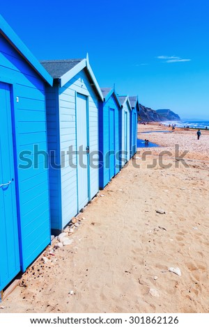 row of blue and white cabanas at the beach of Charmouth, Dorset, England - stock photo