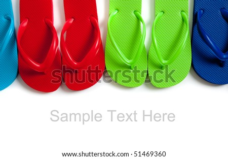 Row of blue, green, red and turquoise flip-flops on a white background and copy space