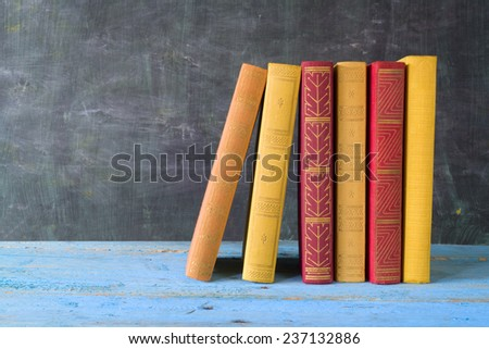 row of books in front of a black board, free copy space - stock photo