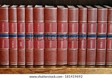 row of books with brown cover on a shelf with titles in Italian
