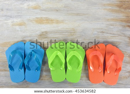 row of bright colored flip-flops on rustic wood - stock photo