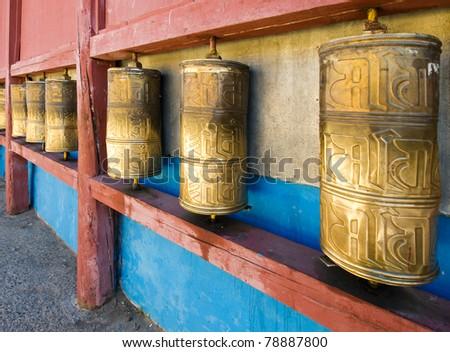 Row of buddhist prayer wheels in Gandan Monastery, Mongolia - stock photo