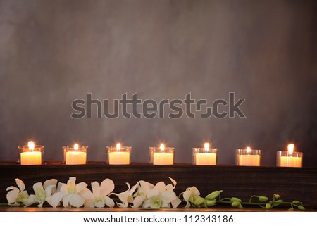 Row of burning candles with white orchid flower,zen concept. - stock photo