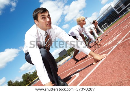 Row of business people getting ready for race with man at foreground - stock photo
