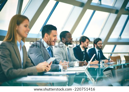 Row of business people listening to presentation at seminar in conference hall - stock photo