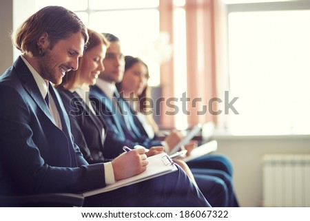 Row of business people making notes at seminar with young man on foreground - stock photo