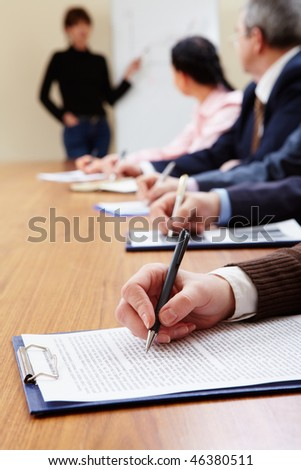 Row of business people making notes during presentation - stock photo