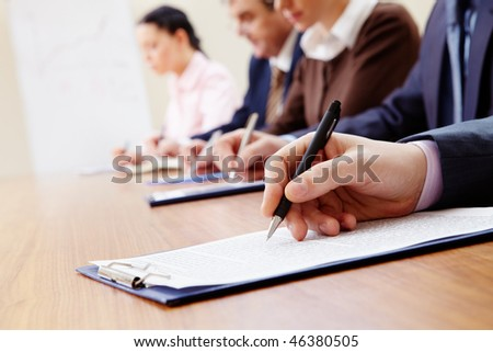 Row of business people making notes with focus on hand holding pen - stock photo
