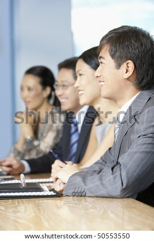 Row of business people sitting at table in conference room - stock photo