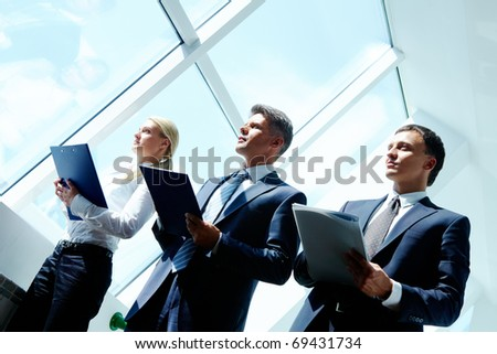 Row of business team holding clipboards and standing in the office