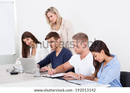 Row of businesspeople studying at desk in office - stock photo