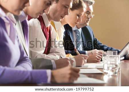 Row of businesspeople writing review of their work with senior boss at background - stock photo