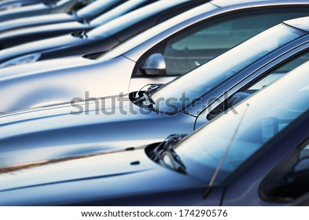 row of cars on a parking lot  - stock photo