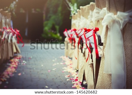 Row of chairs decorated for a wedding - stock photo