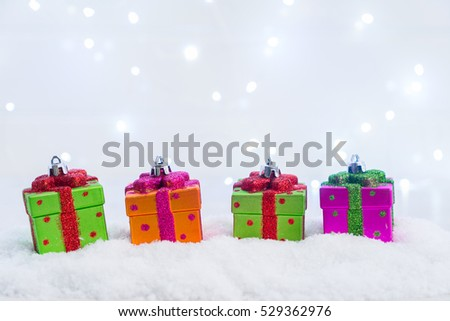 Row of Christmas presents in snow with lights bokeh in background