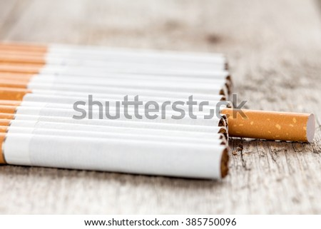 Row of cigarettes  on wooden background with selective focus