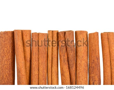 row of cinnamon sticks, over white background