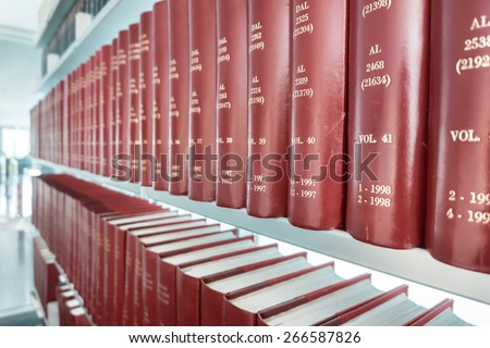 row of classic books in modern office bookshelf - stock photo