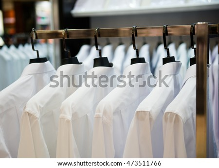 row of cloth hangers with shirts