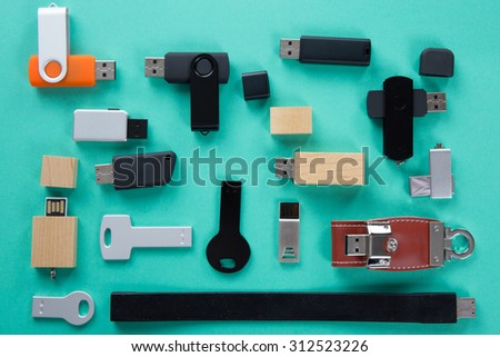 Row of color USB flash drives on green background - stock photo