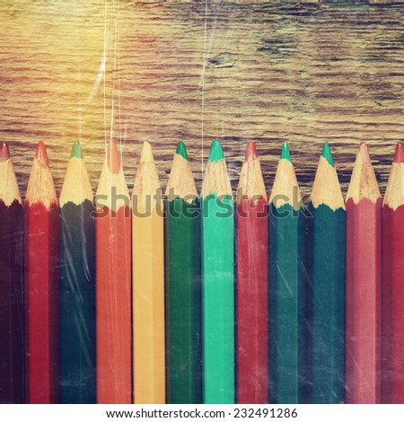 Row of colored drawing pencils closeup on old desk. Vintage stylized image. - stock photo