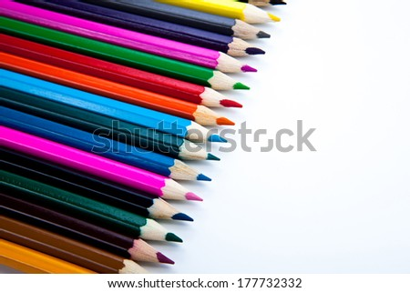 row of colored pencils close-up on white