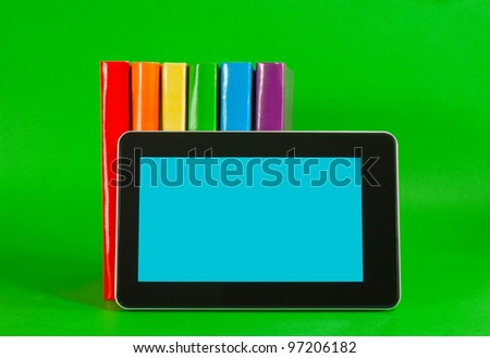 Row of colorful books and tablet PC over green background - stock photo
