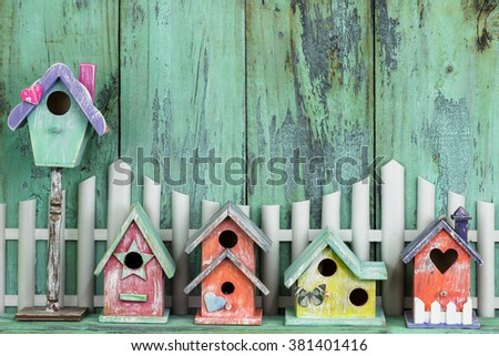 Row of colorful spring birdhouses by white picket fence with antique rustic mint green wood background - stock photo