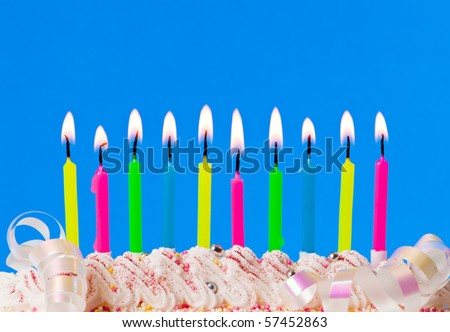 Row of colourful lit candles on decorated cake with streamers