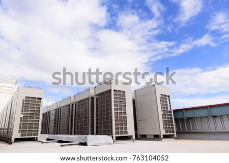 Row of compressor air conditioner on the roof high building with white clouds and blue sky background.