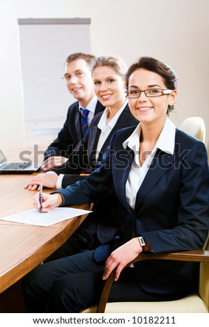 Row of confident white collar workers sitting at the table - stock photo