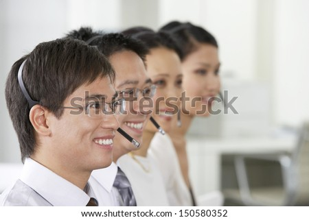 Row of customer service operators wearing headsets in office - stock photo