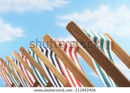 Row of deck chairs on beach close up - stock photo