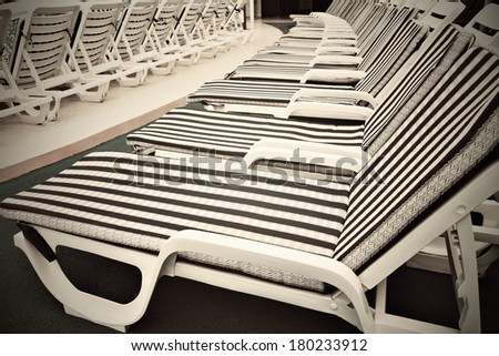 Row of deck chairs on sundeck of the cruise ship at swimming pool - stock photo