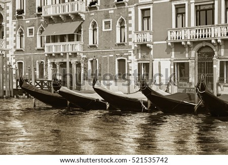 Row of docked venetian gondolas in black and white. Gondolas are very popular sort of entertainment in Venice, Italy