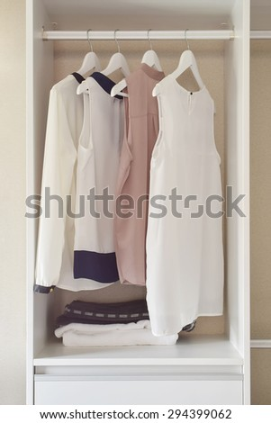 row of dress hanging on coat hanger in white wardrobe - stock photo