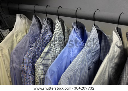 Row of dress shirts hanging on hangers in closet choice of clothing - stock photo