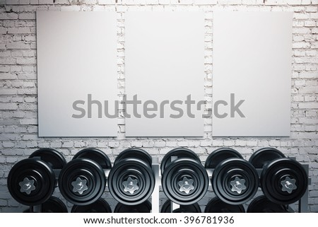 Row of dumbbells and three blank posters on brick wall background. Mock up - stock photo