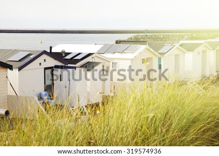 Row of Dutch beach houses with warm sun effect - stock photo