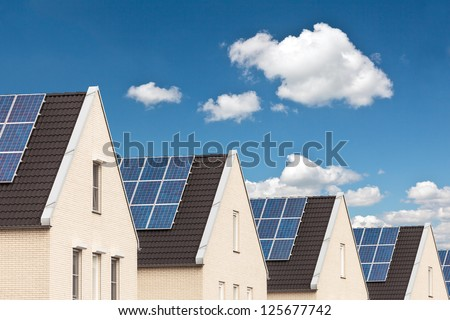 Row of Dutch new houses with solar panels attached on the roofs - stock photo