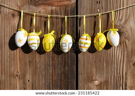 Row of easter eggs along wooden wall  - stock photo