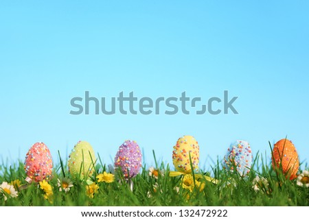 Row of easter eggs with flowers hide in  grass. - stock photo