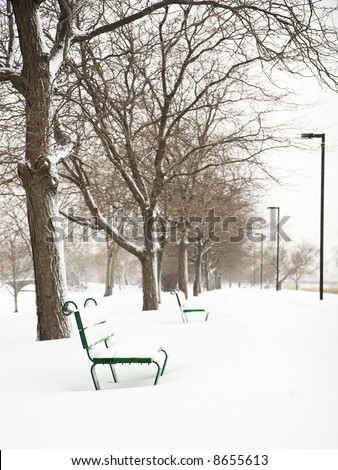 Row of empty benches in a snow storm, along Charles River in Boston