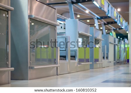 Row of empty check-in desks with computers in airport - stock photo