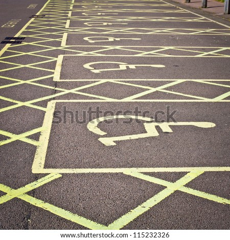 Row of empty disabled parking spaces in a parking lot - stock photo