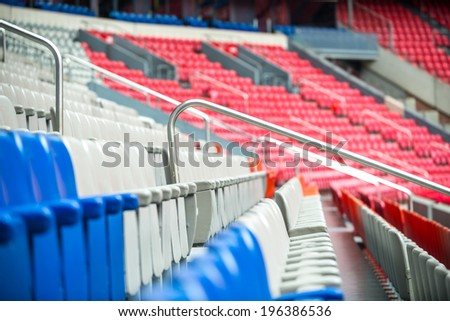 Row of empty red, white and blue chairs in a sporting stadium. - stock photo