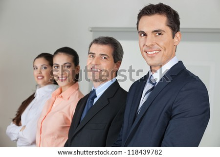 Row of four happy businesspeople in the office - stock photo