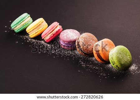 Row of french colorful macaroons with powdered sugar, lying on black background - stock photo